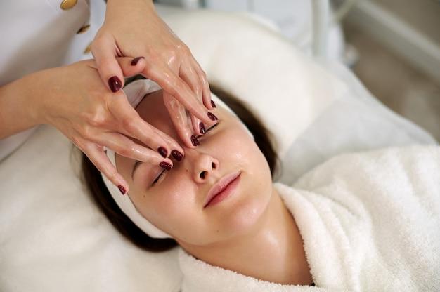 Mani dello specialista di cosmetologia che fa massaggio lifting facciale per donna abbastanza giovane nel salone spa