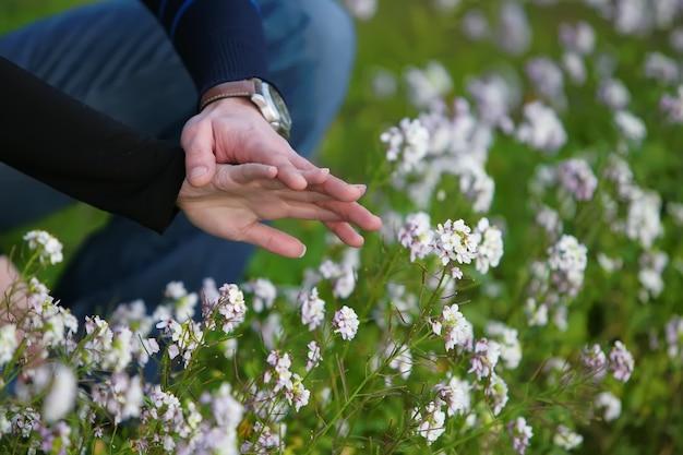 Mani di una coppia che tocca i fiori bianchi
