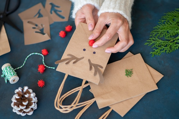 Mani che creano adorabili sacchetti regalo natalizi decorati con renne