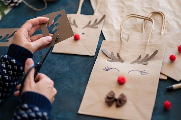 Mani che creano adorabili sacchetti di carta natalizi decorati con renne