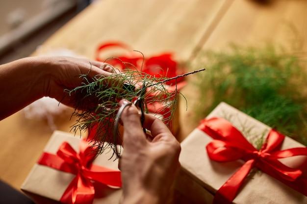 Mani di donna irriconoscibile ritagliata che imballano il regalo di natale, regali di carta kraft di imballaggio ecologico, confezione femminile di un regalo di natale, confezione regalo