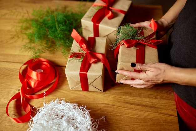 Mani di donna irriconoscibile ritagliata che imballano il regalo di natale