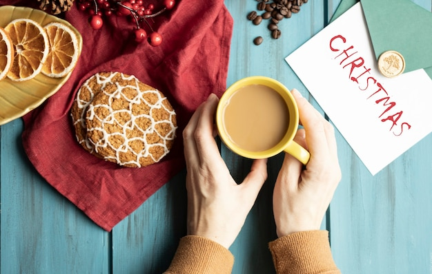 Mani, tazza di cappuccino su una tavola di natale decorata