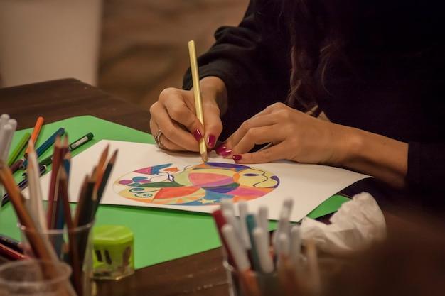 Mani curate da una donna che disegna un mandala a un tavolo pieno di oggetti da disegno in una scuola di arteterapia.