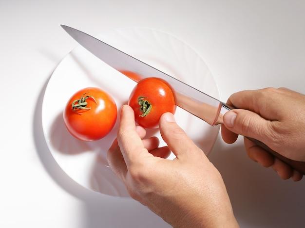Le mani hanno tagliato il pomodoro rosso con il coltello sul piatto bianco