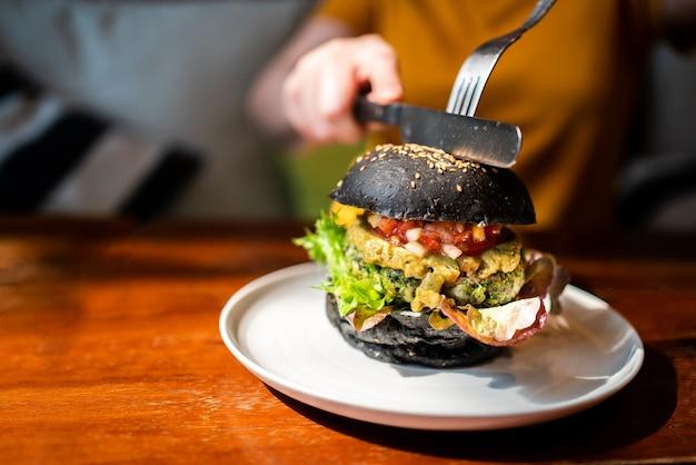Mani taglia hamburger di carbone di legna di quinoa broccoli condita con guacamole, salsa di mango e insalata fresca con coltello e forchetta.
