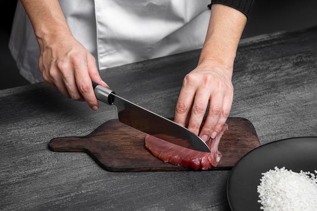 Mani che tagliano il pesce con il coltello