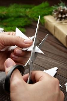 Mani che tagliano i fiocchi di neve del libro bianco sulla tavola di legno