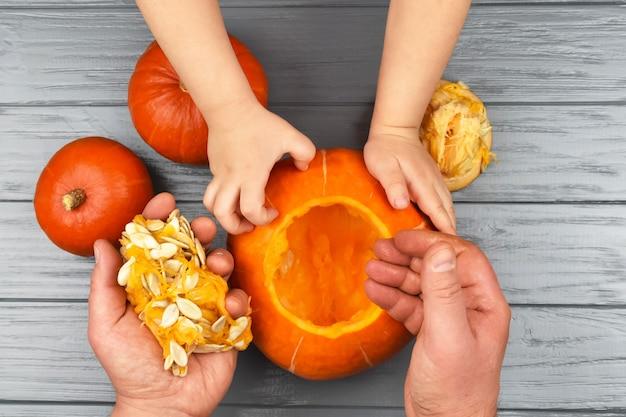 Le mani di una figlia e di un padre che tirano semi e materiale fibroso da una zucca
