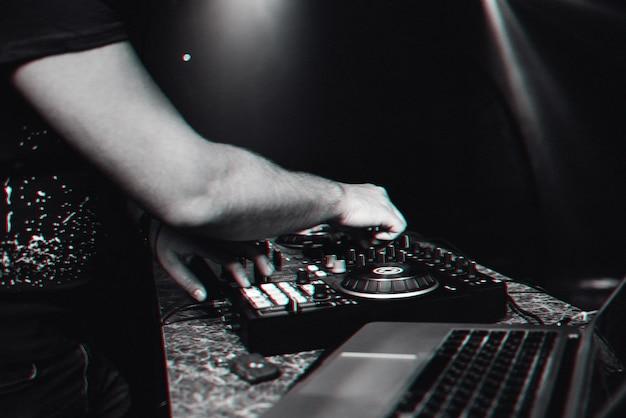Mani dj che suona musica contemporanea elettronica sulla console del mixer durante un concerto in una discoteca