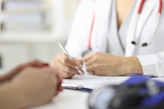 Mani del medico e del paziente sul tavolo di lavoro nel concetto di esame medico dell'ufficio medico
