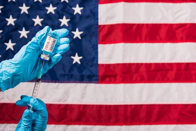 Le mani del medico indossano guanti che tengono il vaccino e la siringa della fiala di coronavirus (covid-19) sulla bandiera degli stati uniti d'america
