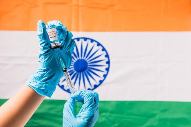 Le mani del medico indossano guanti che tengono il vaccino e la siringa della fiala di coronavirus sulla bandiera dell'india