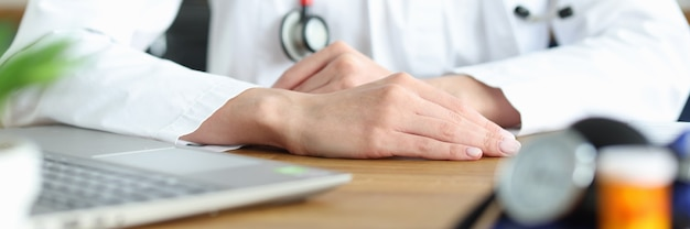 Mani del medico in camice bianco sul posto di lavoro