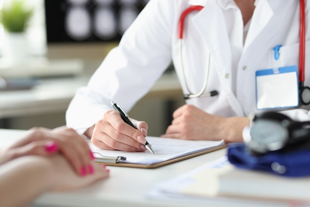Mani del medico che scrivono in una tessera sanitaria del paziente