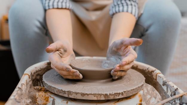 Mani che fanno primo piano di ceramiche
