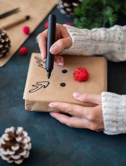 Mani che disegnano renna carina sul regalo di natale