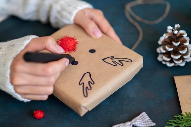 Mani che disegnano simpatiche renne sul regalo di natale