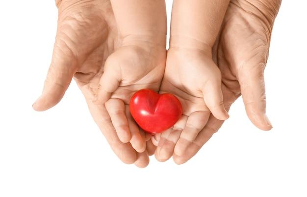 Mani dell'uomo anziano e del bambino con il cuore su priorità bassa bianca