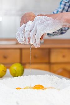 Mani di un uomo anziano che rompono un uovo in farina per fare l'impasto su un tavolo in cucina
