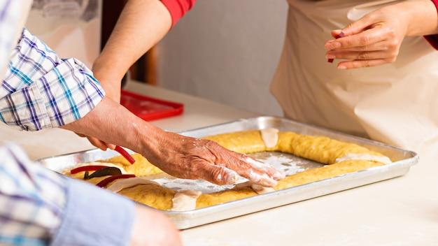 Mani di un uomo anziano e di una giovane donna che decorano l'impasto su un vassoio di metallo per fare il pane