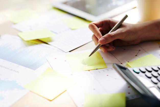 Mani dell'imprenditore che scrivono idee su adesivi gialli quando si lavora con i rapporti al tavolo dell'ufficio