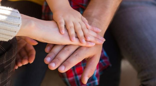 Mani di padre, madre, tieni la mano piccolo bambino. i genitori tengono le mani del bambino. primo piano della mano del bambino nelle mani dei genitori. concetto di unità, sostegno, protezione, felicità. primo piano della mano del bambino nei genitori
