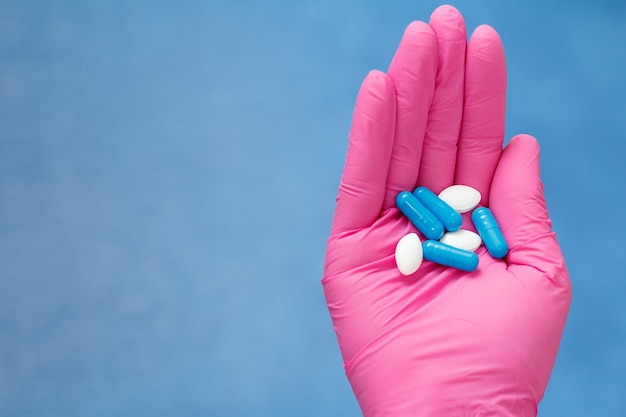 Mani della dottoressa in guanto rosa con mucchio di pillole di colore diverso. concetto di negozio di droga legale