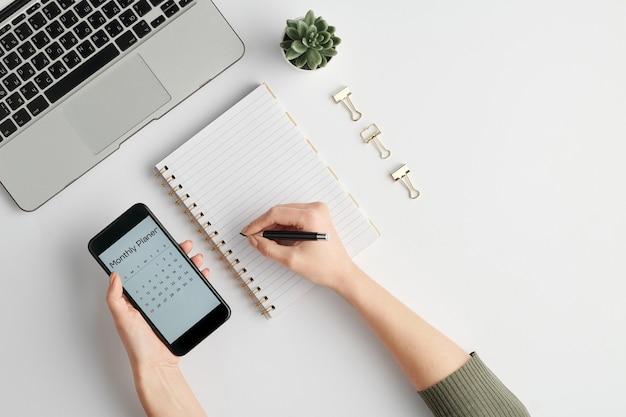 Mani dell'impiegato femminile che tiene smartphone con pianificatore mensile sullo schermo e penna sulla pagina vuota del taccuino