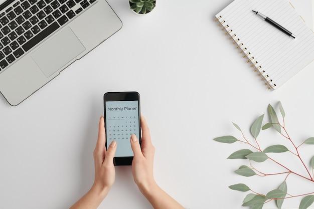 Mani dell'impiegato femminile che tiene smartphone con pianificatore mensile sullo schermo sopra la scrivania bianca durante il lavoro
