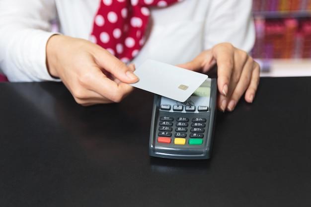 Mani di un commesso femminile che tiene una carta di credito e un makin