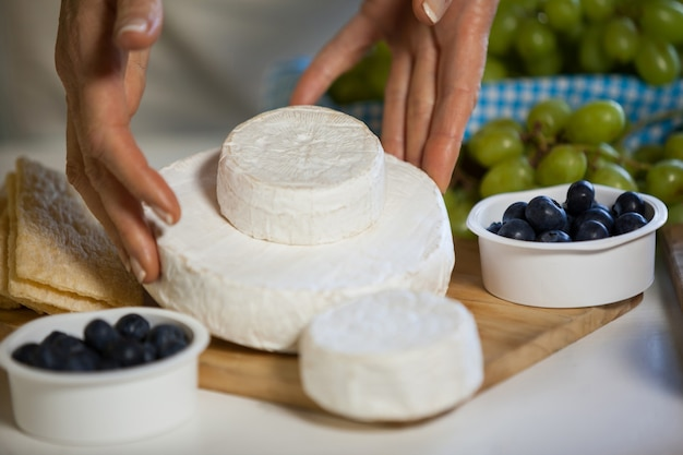 Mani del personale femminile che organizza il formaggio al bancone