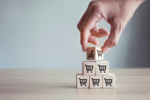 Le mani capovolgono il cubo con il grafico dell'icona e l'aumento del volume di vendita del simbolo del carrello della spesa fanno crescere il business