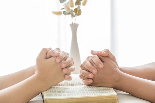 Mani giunte in preghiera su una sacra bibbia nel concetto di chiesa per fede, spiritualità e religione, donna che prega sulla sacra bibbia al mattino. mano della donna con la preghiera della bibbia.