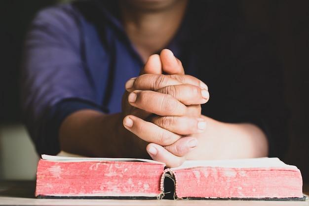 Mani giunte in preghiera su una sacra bibbia in concetto di chiesa per fede, spiritualità e religione