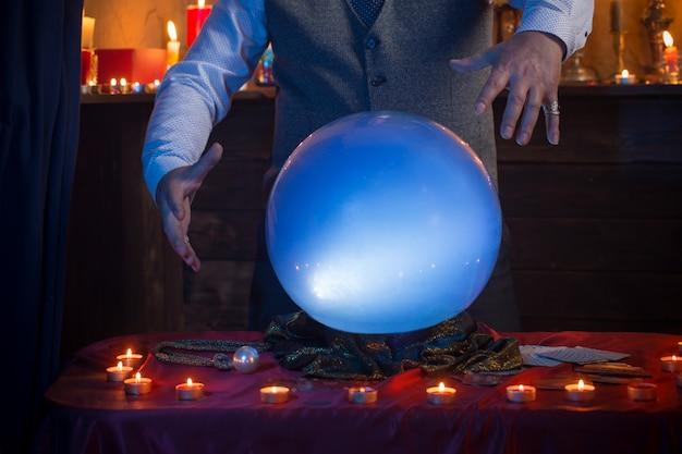 Mani dell'indovino con sfera di cristallo illuminata