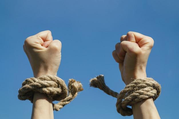 Le mani libere dalle catene sono tese verso il cielo azzurro con una sensazione di libertà
