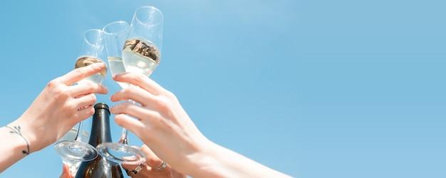 Mani di amici, colleghi mentre bevono vino o champagne, si divertono, tintinnano bottiglie, bicchieri insieme.
