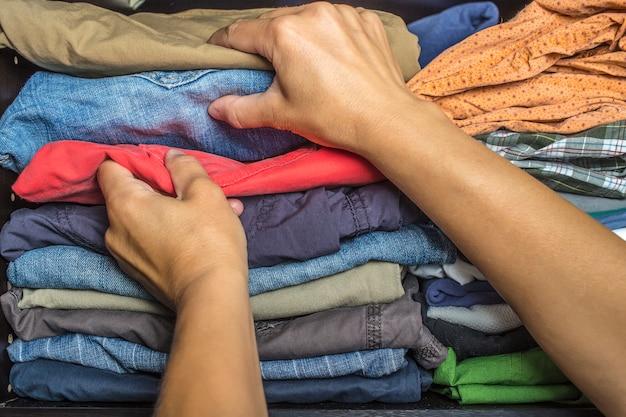 Mani che tirano fuori i vestiti dall'armadio