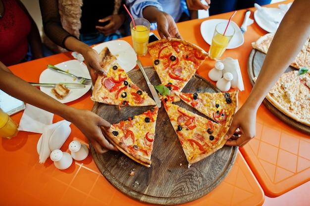 Mani dei gilrls che prendono le fette della pizza sul ristorante