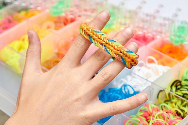 Le mani della ragazza tengono un braccialetto di elastici