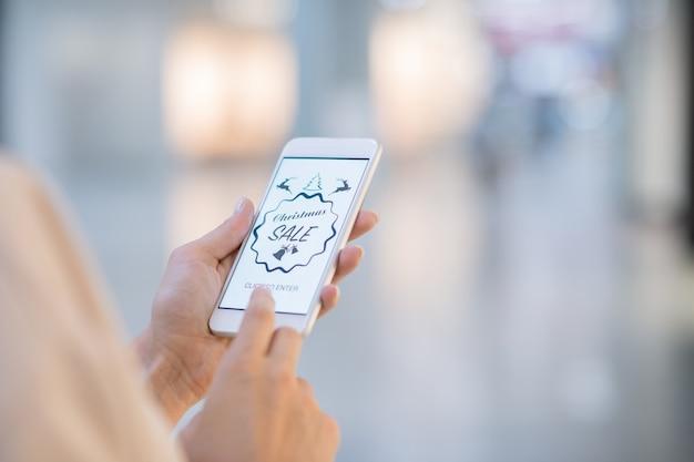 Mani della ragazza che tiene smartphone e sta per entrare nel negozio online per guardare tra gli articoli in vendita di natale