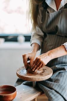 Mani di una ragazza su un tornio da vasaio con argilla. il processo di creazione della ceramica.