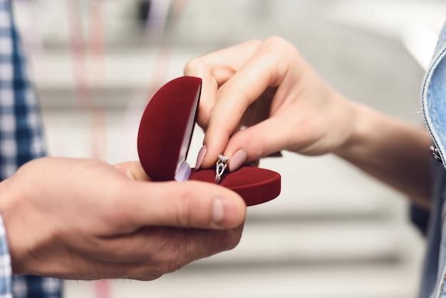 Le mani della ragazza prendono l'offerta di matrimonio dell'anello di fidanzamento.