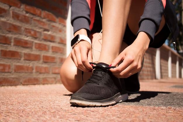 Le mani di una ragazza che si allaccia le scarpe