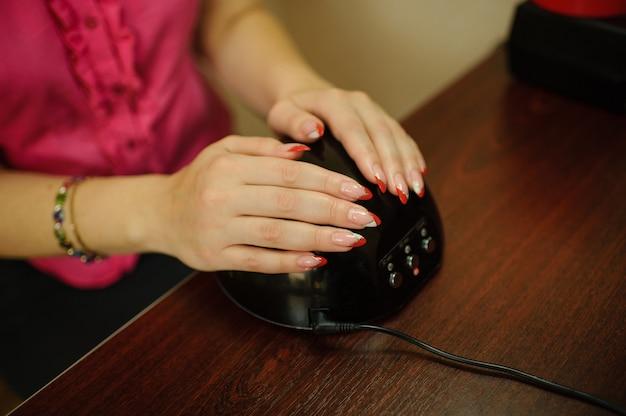 Mani di una ragazza con una delicata manicure su una macchina per l'essiccazione uv. cura delle unghie dopo la verniciatura.