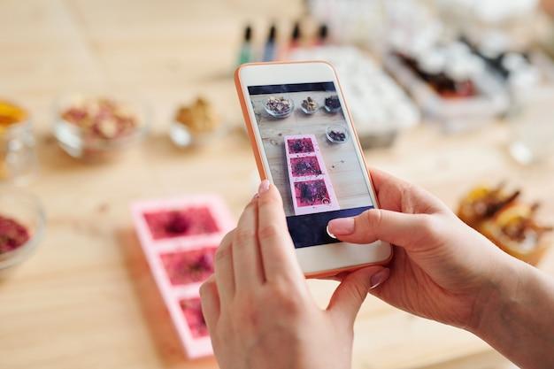 Mani della ragazza con lo smartphone che cattura foto di sapone fatto a mano in stampi in silicone sulla tavola di legno in studio