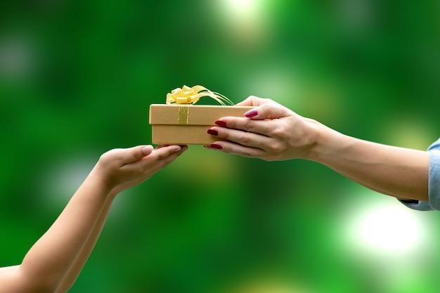 Le mani danno un regalo congratulazioni grazie sfondo verde