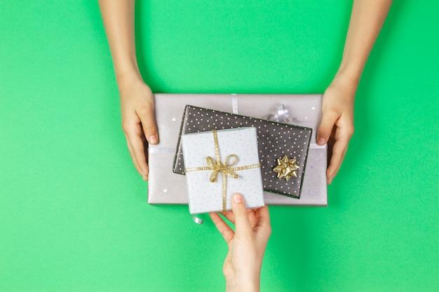 Le mani danno e prendono le scatole dei regali su sfondo verde chiaro