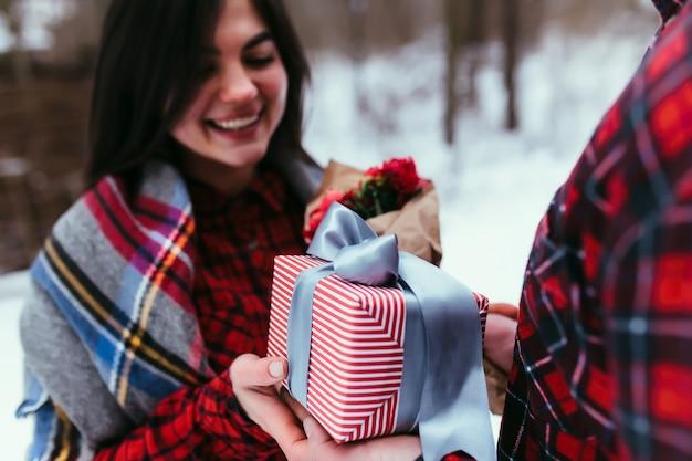 Mani che danno una confezione regalo con nastro. sfondo sfocato.